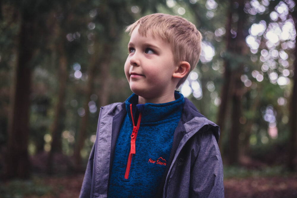 Child wearing a Peter Storm fleece and coat exploring the woodlands in Autumn